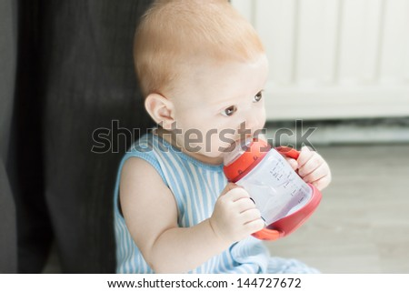 Baby drinking water from cup/bottle - stock photo
