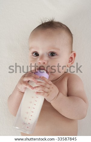 Baby drinks from a baby-bottle all by herself