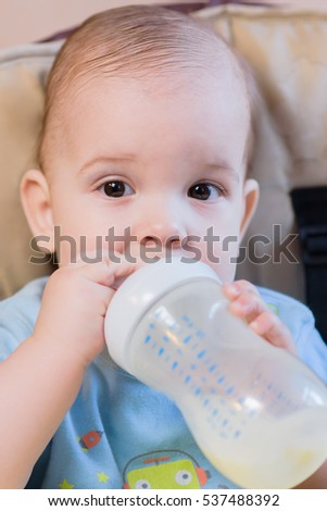 baby drinks from a bottle of milk in the house