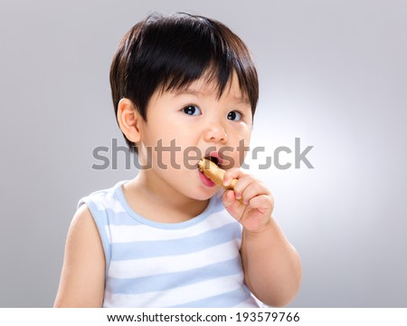 Baby eating biscuit - stock photo