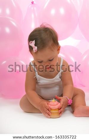 Baby eating her birthday cupcake - stock photo