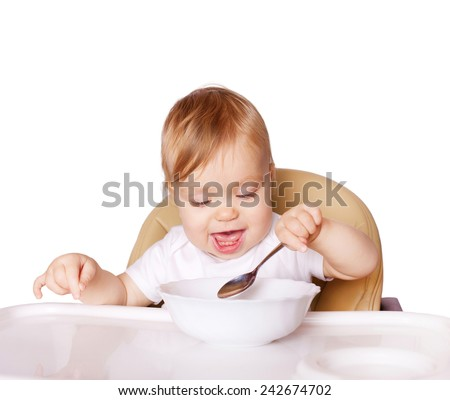Baby eating with the left hand and sitting in a high chair for feeding. Isolated on white background. - stock photo
