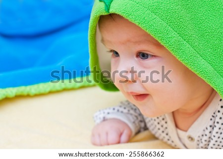 Baby enjoying being covered with a warm fluffy blanket. - stock photo