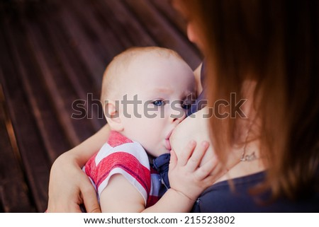 Baby feeds on his mother's breasts - stock photo
