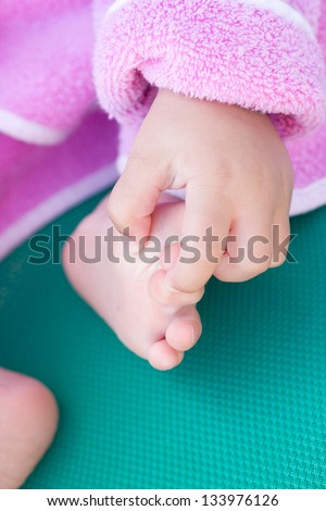 Baby feet and hand - stock photo