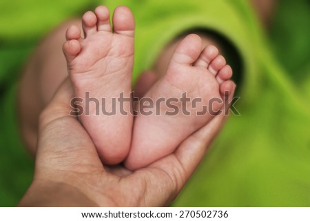 Baby Feet and mom hand - stock photo