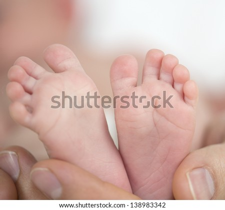 Baby feet at 4 weeks and adult man hands holding them.