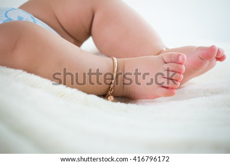 baby feet close up with  Anklet - stock photo