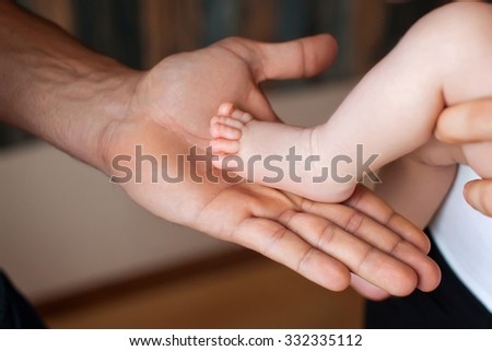 Baby feet in fother hands. Tiny Newborn Baby's feet on female shaped hands closeup. Dad and her Child. Happy Family concept. - stock photo