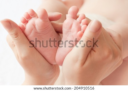 Baby feet in mommy's hands, shallow DOF. - stock photo