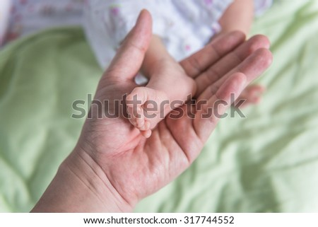 Baby feet in mother hand