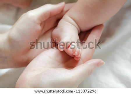 Baby feet in mother hands close up