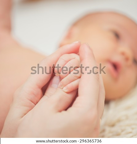Baby feet in mother hands. Mom and her Child. Happy Family concept.