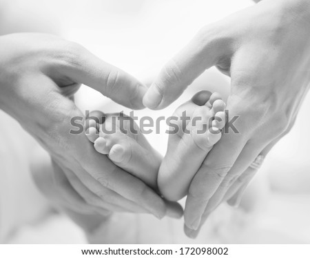 Baby feet in mother hands. Tiny Newborn Baby's feet on female Heart Shaped hands closeup. Mom and her Child. Happy Family concept. Beautiful Black and White conceptual image of Maternity