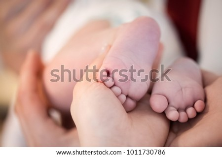 baby feet in mother's hands