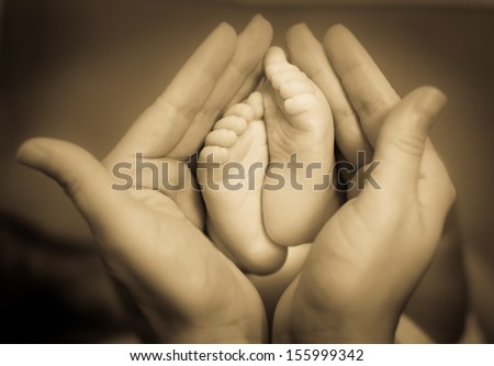Baby feet in mother's hands - stock photo