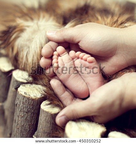 Baby feet in mother's hands gentle in the cradle of red fur and wood - stock photo