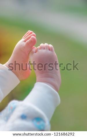 baby feet in outdoor, selective focus - stock photo