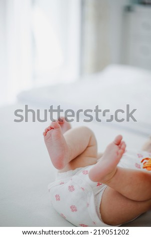 baby feet on the bed over white room background - stock photo