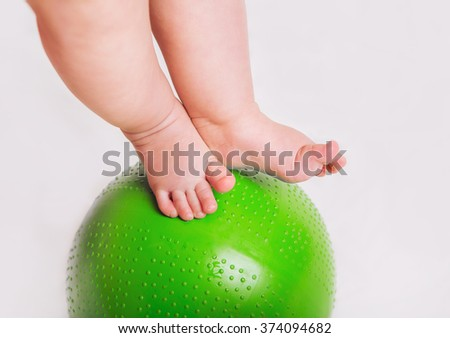 Baby feet on the green ball