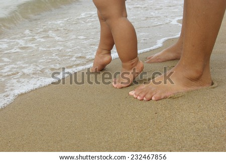 Baby feet walking and mother foot on the beach