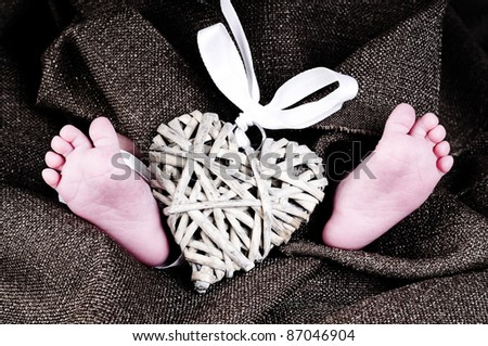 baby feet with a heart with ribbon - stock photo