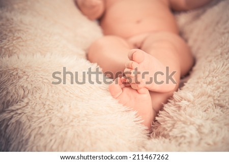 baby feet with toes curled up, on white fur background