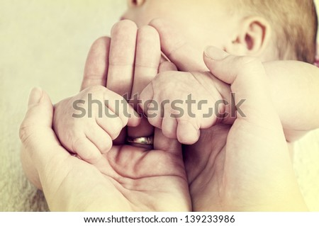 Baby fists in the mother hands - stock photo