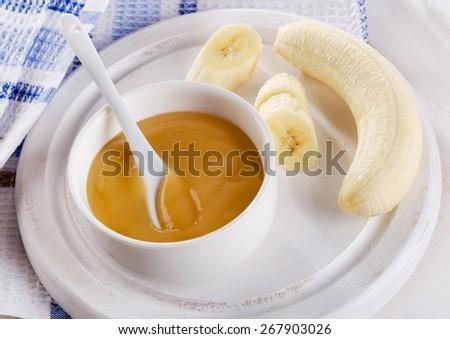 Baby food - bananas puree in  a bowl. Selective focus - stock photo