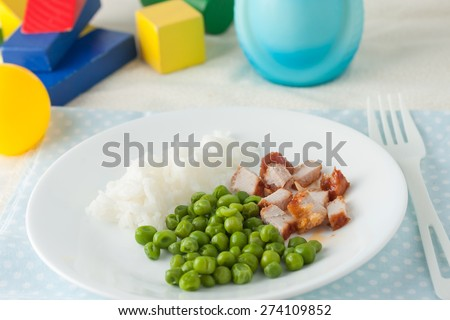 baby food: finely chopped tender cutlet and green peas on white plate - stock photo