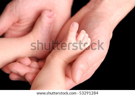 Baby foot in mother's hands on black background - stock photo