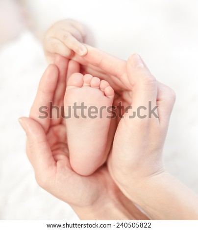 baby foot in mother's hands with care - stock photo