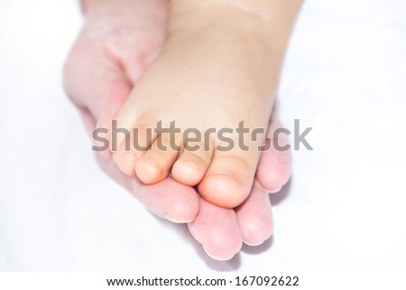 Baby foot in the mother hand - stock photo