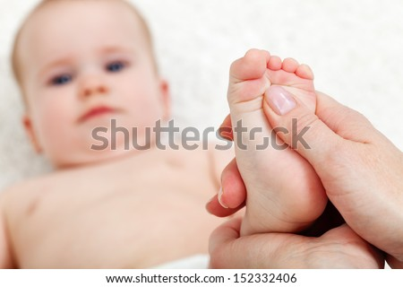 Baby foot massage - mother hands pampering child - stock photo