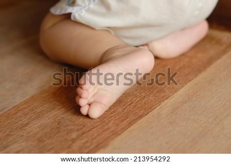 baby foot on wooden floor  - stock photo