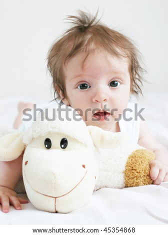 Baby - four months old girl and sheep
