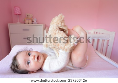 Baby (girl age 06 months)  plays with soft toy in her bedroom. Concept photo toys and children. - stock photo