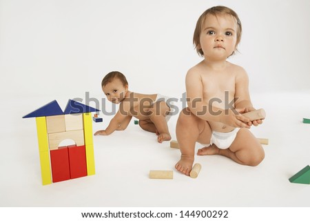 Baby girl and baby boy playing with building blocks isolated on white background - stock photo