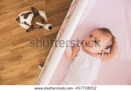 Baby girl and jack russel terrier dog at home. - stock photo