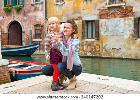 Baby girl and mother poiting on copy space while in venice, italy - stock photo