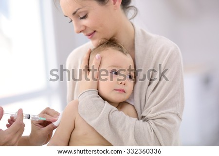 Baby girl at doctor's office receiving vaccine injection - stock photo
