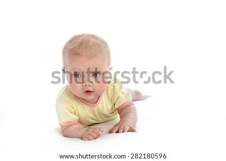 baby girl child lying down on white blanket  portrait face studio shot isolated on white caucasian yellow clothing - stock photo