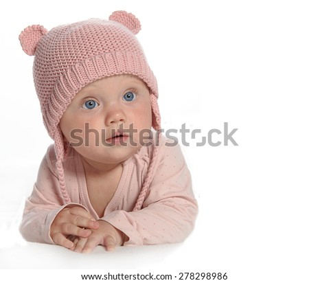 baby girl child lying down on white blanket warm hat pink fashion portrait face studio shot isolated on white caucasian