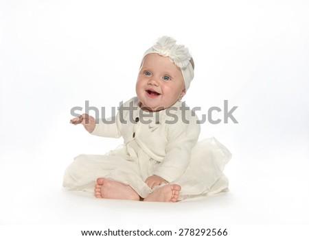 baby girl child sitting down on white blanket smiling happy white dress fashion portrait face studio shot isolated on white caucasian - stock photo