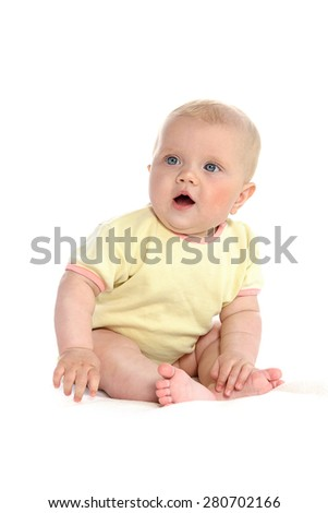 baby girl child sitting down on white blanket smiling happy yellow clothing portrait face studio shot isolated on white caucasian - stock photo