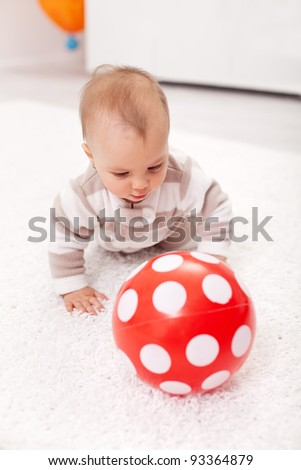 Baby girl crawling on the floor chasing a red ball - stock photo