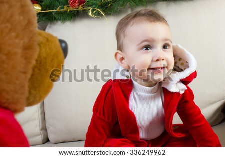 Baby girl dressed in a Christmas costume with toy teddy bear - stock photo