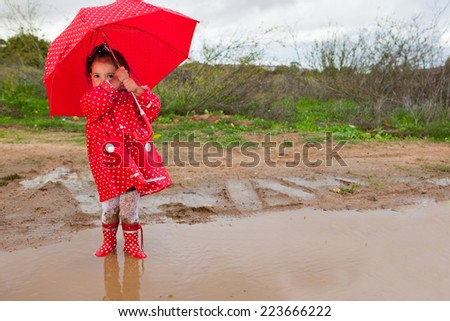 Baby girl dressed with dotted raincoat and umbrella a typical rainy and windy day of autumn - stock photo