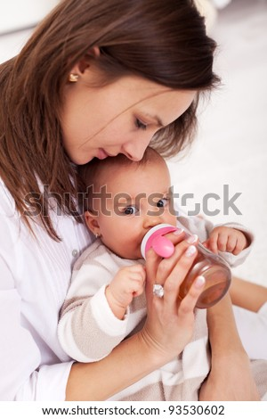Baby girl drinking from plastic bottle sitting in mother lap