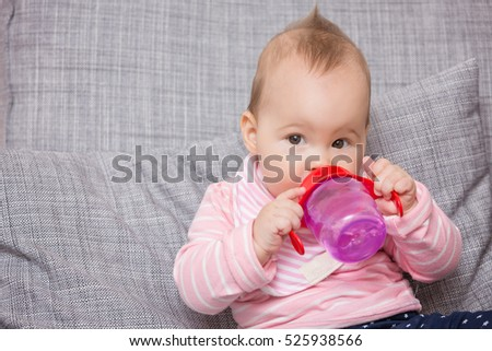 Baby girl drinking water from the red plastic bottle, sitting on a grey sofa
